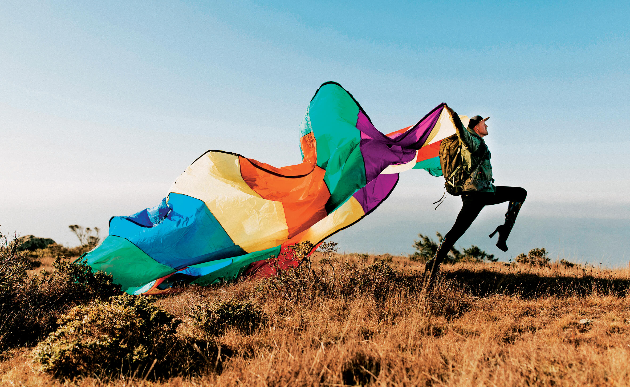 Hiker with rainbow parachute